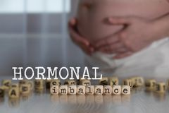 Word HORMONAL IMBALANCE composed of wooden letters. Pregnant woman in the background stock photos