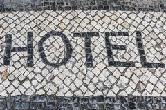 Word Hotel on a Typical Mosaic Floor in Lisbon Street, Portugal Stock Photos