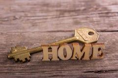 Word huis dat van houten brieven met een sleutel wordt gemaakt stock afbeeldingen