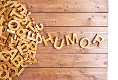 Word humor made with wooden letters. Word humor made with block wooden letters next to a pile of other letters over the wooden board surface composition royalty free stock photography