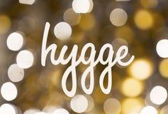 Word hygge over vage gouden lichtenachtergrond Stock Foto's
