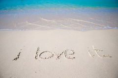 Word i love it handwritten on sandy beach with soft ocean wave on background Stock Photos