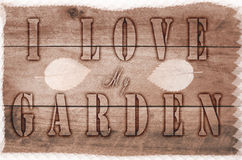 Word I love my garden written, burned letters on wooden brown background Royalty Free Stock Photography