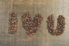 The word I Love You made from coffee beans on wooden table. Still life style and Vintage. Close up of The word I Love You made from coffee beans on wooden table stock photo