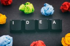 The word Idea on a black background with some colorful crumpled paper balls around it. Idea. The word Idea on a black background with some colorful crumpled royalty free stock image