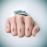 Word idea in the knuckles of a young man Stock Image