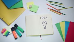 Word Idea and light bulb written on white note pad stock video