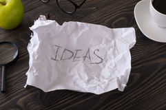 Word idea written in pencil on crumpled sheet of paper Stock Images