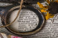 Imagine centered in old pair of scissors with dried flowers. The word imagine centered in old pair of scissors with dried flowers, decorative paper and jute royalty free stock photography