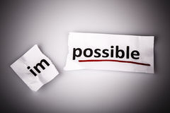 The word impossible changed to possible on torn paper Stock Image