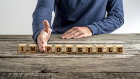 The word Impossible - Possible. On a blocks separated by the hand of a man on rustic old wooden desk Royalty Free Stock Image