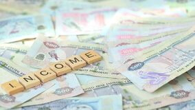 Word `income` from wooden blocks on paper money in UAE dirhams