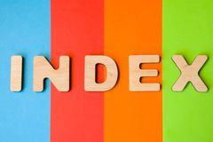 Word Index of large wooden letters on colored background of 4 colors: blue, orange, red and green. Use of word Index internet, dat. Abase, SEO, science Stock Photography