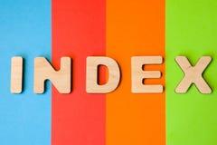 Word Index van grote houten brieven op gekleurde achtergrond van 4 kleuren: blauw, sinaasappel, rood en groen Gebruik van woordin stock fotografie