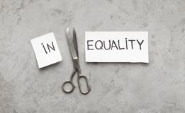 Word Inequality cut with scissors to two parts. In and Equality, gray background, top view stock images