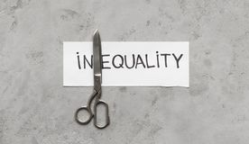 Word Inequality devided with scissors into two parts. In and Equality, gray background, top view royalty free stock photos