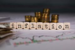 Word INFLATION composed of wooden letter. Stacks of coins in the background. Closeup royalty free stock image