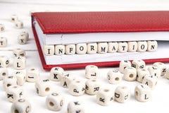 Word Informatie in houten blokken in rood notitieboekje wordt geschreven over whi die Stock Foto's