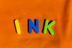 The word Ink composed from letters. The word Ink composed from colorful children toy big letters on the grass stock photography