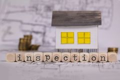 Word INSPECTION composed of wooden letter. Small paper house in the background. Closeup royalty free stock image