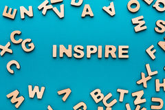 Word Inspire on blue background. With pile of wooden letters. Creativity, imagination concept stock photo