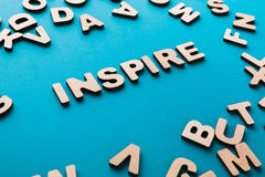 Word Inspire on blue background. With pile of wooden letters. Creativity, imagination concept Royalty Free Stock Images