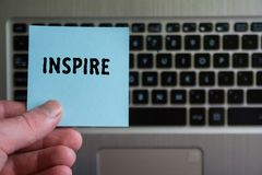 Word INSPIRE on sticky note hold in hand on keyboard background royalty free stock photos