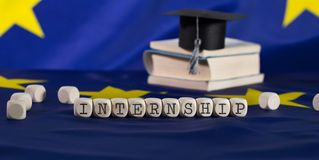 Word INTERNSHIP composed of wooden dices. Black graduate hat on EU flag in the background. Closeup stock photography