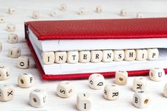 Word Internship written in wooden blocks in red notebook on white wooden table. Wooden abc royalty free stock photo