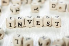 Invest word written on wood block. Stock Image