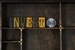 Word invest in wooden letterpress type. With silver coin  in dark wood box Royalty Free Stock Photos