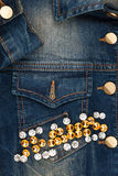 Word jeans made of rhinestones on denim jacket Stock Photos