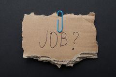 The word `Job?` on a piece of cardboard box on a black background. The word `Job?` on a piece of cardboard box on a black background royalty free stock photography