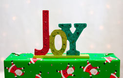 The word JOY on a Christmas present. The word JOY in colorful painted glitter is on top of a wrapped Christmas gift. Background is white with little lights Stock Images