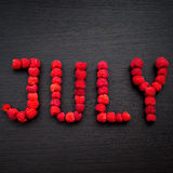 Word July of raspberries on table Royalty Free Stock Photos