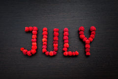 Word July of raspberries on table Royalty Free Stock Photo