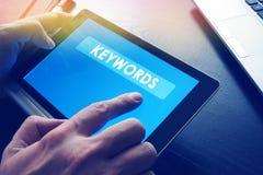 Word Keywords on a tablet. Word Keywords on a tablet as a part of SEO Stock Photos