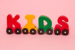 Word kids made of letters train alphabet. Bright colors of red yellow green and blue on a white background. Early childhood develo stock images