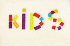 Word of KIDS shaped by colorful toy bricks stock images