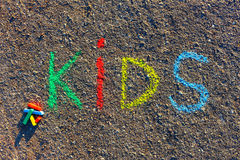 Word KIDS written with colorful crayons on the asphalt, ground. Royalty Free Stock Image
