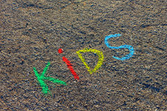 Word KIDS written with colorful crayons on the asphalt, ground. Royalty Free Stock Images