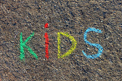 Word KIDS written with colorful crayons on the asphalt, ground. Stock Photo