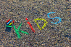 Word KIDS written with colorful crayons on the asphalt, ground. royalty free stock photography