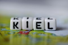 Word KIEL formed by alphabet blocks on atlas map. Geography Royalty Free Stock Photo