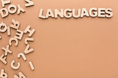 Word Languages with pile of english letters. Word Language with pile of English letters on beige background, copy space. English language learning concept Stock Image