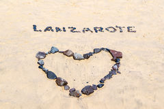 Word Lanzarote and a heart written with black stones on a beach Royalty Free Stock Images