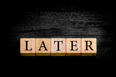 Word LATER isolated on black background with copy space Stock Photography