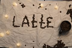A word `Latte` is laid out by coffee grains stock photos