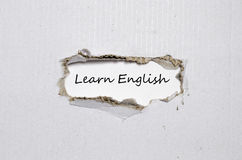 The word learn english appearing behind torn paper Royalty Free Stock Photography