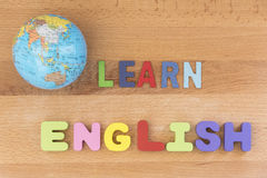 Word learn english with globe over wooden background. Education concept, top view Royalty Free Stock Images